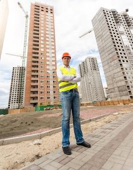 Młody inżynier budowlany stojący przed budynkami w trakcie budowy