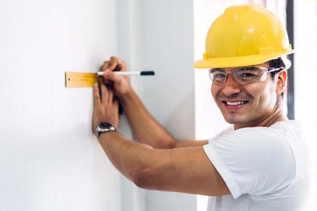 Młody inżynier budowlany w żółtym hełmie pracuje i patrzeje pracę dla planować projekt przy budować stronę domową