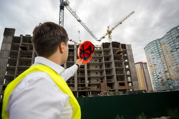 Młody inżynier budowlany z czerwonym kaskiem wskazującym na budynek w budowie