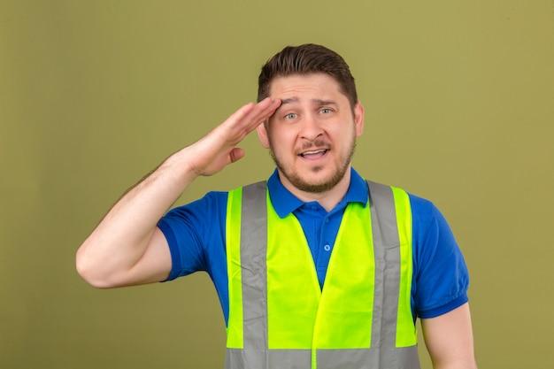 Młody inżynier człowiek ubrany w kamizelkę budowlaną patrząc na kamery z pewnym uśmiechem, salutując ręką nad głową na na białym tle zielonym tle