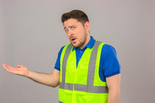 Młody inżynier człowiek ubrany w kamizelkę budowlaną, patrząc zdezorientowany stojąc z ręką podniesioną, mając wątpliwości na na białym tle