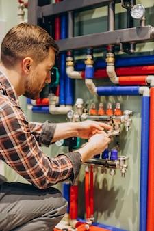Młody inżynier dostosowujący autonomiczne ogrzewanie