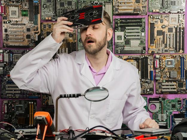 Młody inżynier elektronik, siedząc przy stole laboratoryjnym, chłodzi czoło chłodnicą komputera