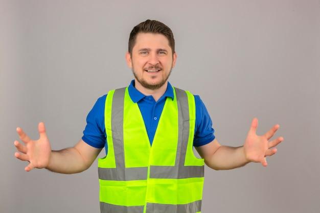 Młody inżynier mężczyzna ubrany w kamizelkę budowlaną, gestykulując rękami pokazującymi duży i duży symbol środka znaku wielkości uśmiechnięty patrząc na kamery na białym tle