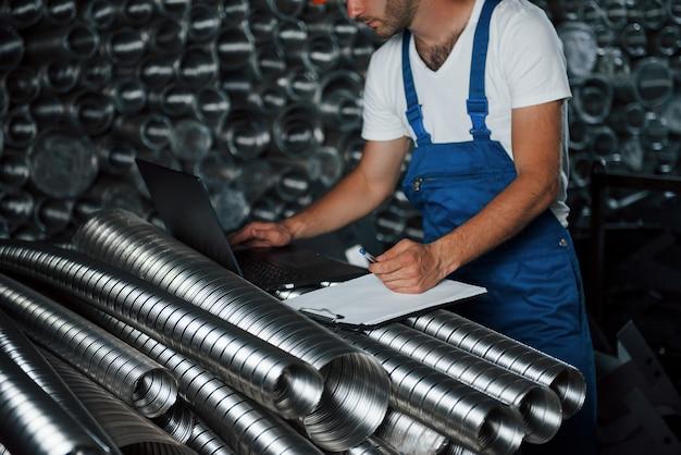 Młody inżynier. mężczyzna w mundurze pracuje nad produkcją. nowoczesna technologia przemysłowa.