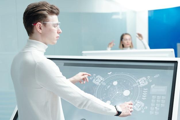 Młody inżynier oprogramowania w inteligentnych goglach stoi przy dużym interaktywnym wyświetlaczu ze schematami holograficznymi i analizuje wirtualne dane