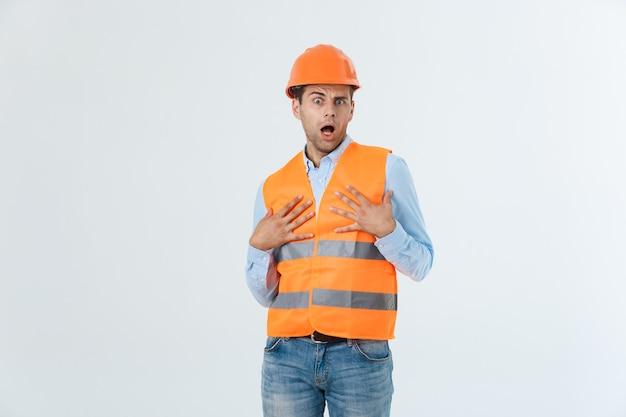 Młody inżynier otwiera usta w szoku, odwracając wzrok, na białym tle na białym tle.