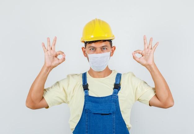 Młody inżynier pokazuje ok gest w mundurze, widok z przodu maski.