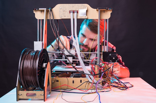 Młody inżynier-projektant korzystający z drukarki 3d w laboratorium i badający prototyp produktu, koncepcję technologii i innowacji.