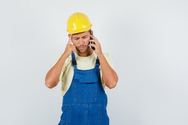 Młody inżynier rozmawia przez telefon komórkowy w mundurze i wygląda zamyślony. przedni widok.
