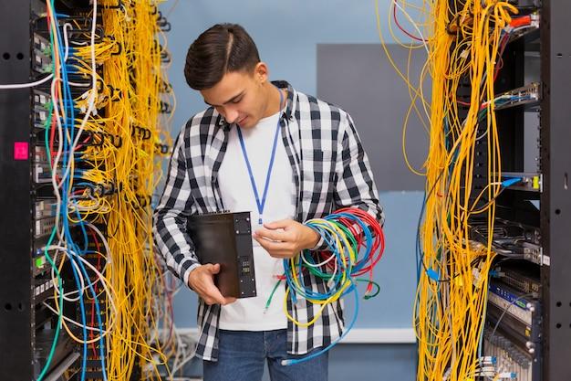 Młody inżynier sieci patrząc na przełączniki ethernet