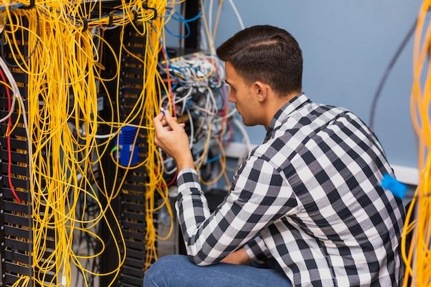 Młody inżynier sieci pracuje z drutami