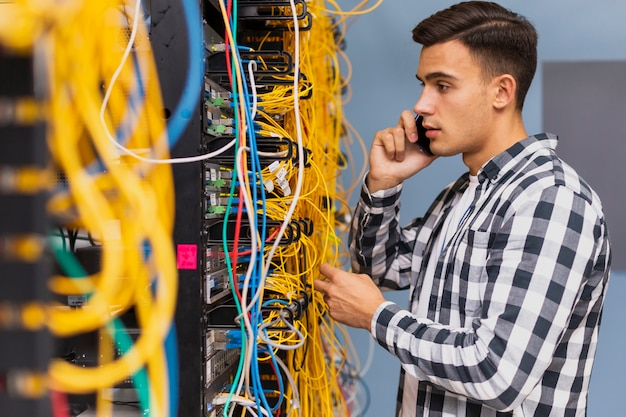 Młody inżynier sieci rozmawia przez telefon