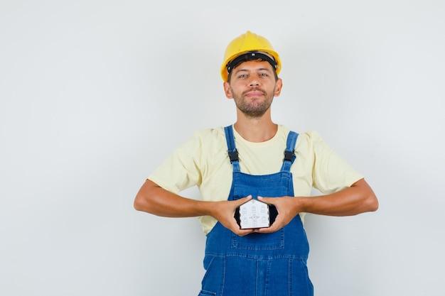 Młody inżynier trzyma model domu w mundurze i wygląda wesoło, widok z przodu.