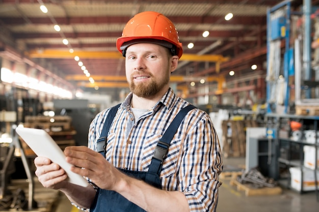 Młody inżynier w kasku i kombinezonie podczas pracy w fabryce szuka danych technicznych w sieci