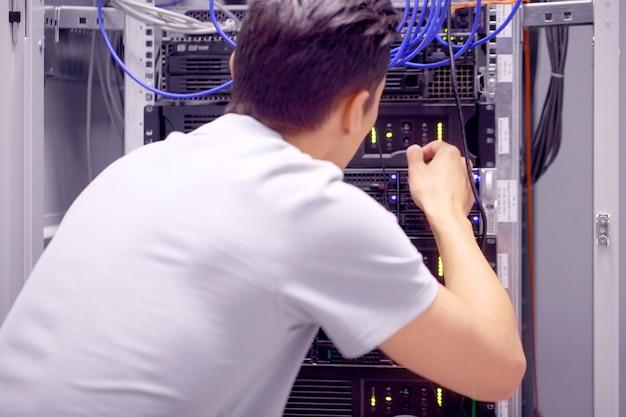 Młody inżynier w serwerowni łączącej przewody