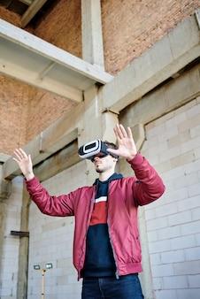 Młody inżynier w zestawie słuchawkowym vr stojący w niedokończonym budynku i oglądający wirtualny przykład nowego domu lub innej konstrukcji