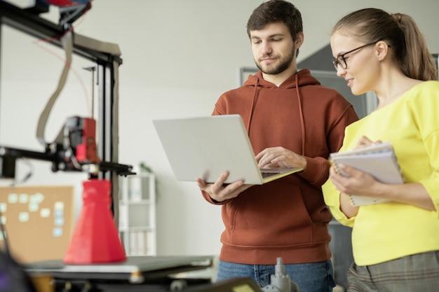 Młody inżynier z laptopem robiącym prezentację i jego ładny kolega zapisujący nowe pomysły na spotkaniu roboczym
