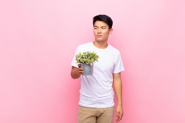 Młody japończyk czuje się smutny, zdenerwowany lub zły i patrzy w bok z negatywnym nastawieniem, marszcząc brwi w niezgodzie, trzymając roślinę