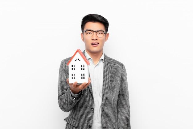 Młody japończyk czuje się zdziwiony i zdezorientowany, z głupim, oszołomionym wyrazem twarzy, patrząc na coś nieoczekiwanego z modelem domu