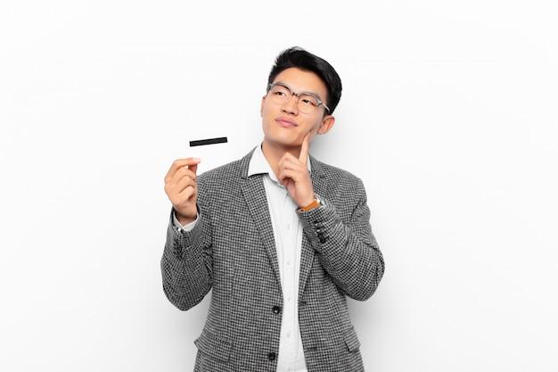 Młody japończyk uśmiecha się radośnie i marzy lub wątpi, patrząc w bok. koncepcja karty kredytowej.