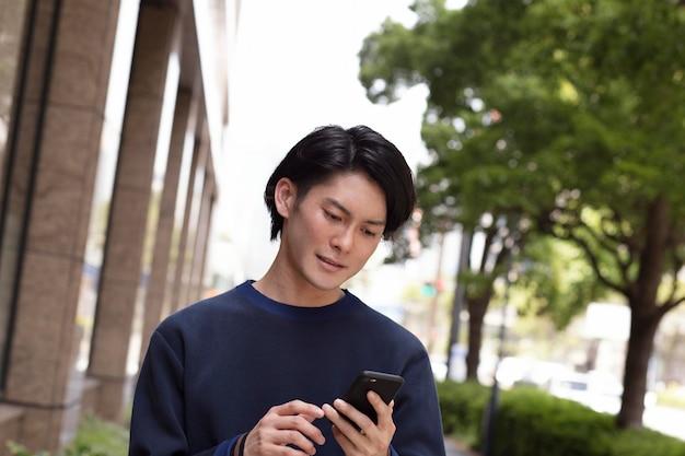 Młody japończyk w niebieskim swetrze na zewnątrz