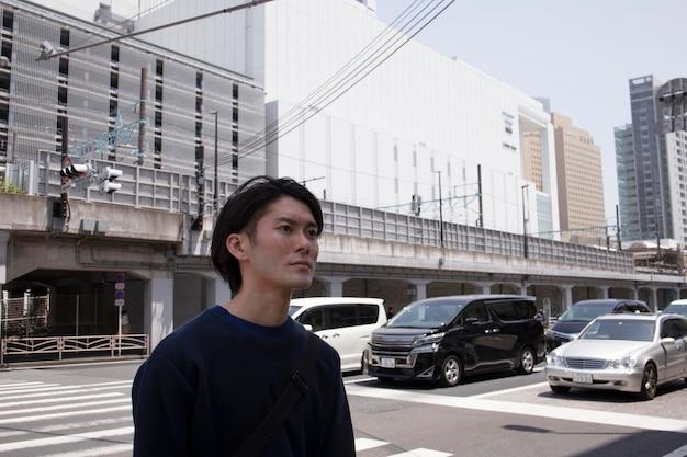 Młody japończyk w niebieskim swetrze w mieście