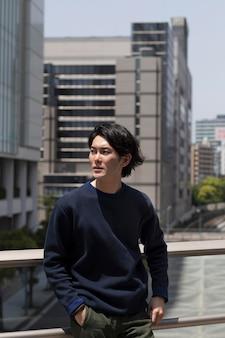 Młody japończyk w niebieskim swetrze