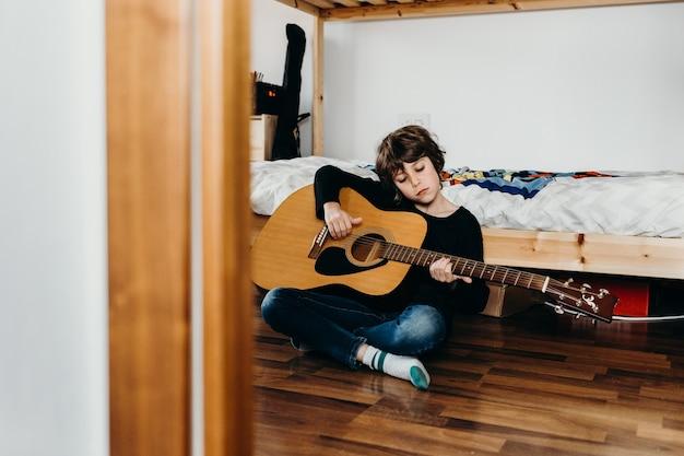 Młody jasnowłosy chłopak siedzi na podłodze i trzyma gitarę