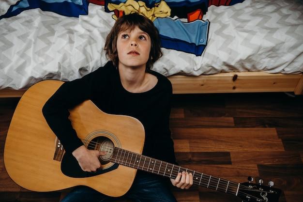 Młody jasnowłosy chłopiec siedzi na podłodze i trzyma gitarę