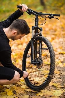 Młody jeździec mężczyzna jeździec ma problem z niskim kołem w parku jesień