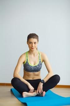 Młody jogin atrakcyjnej kobiety joga ćwiczy pojęcie, będący ubranym sportswear, czarnego podkoszulek bez rękawów i spodnia, pełna długość
