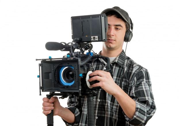 Młody kamerzysta z profesjonalną kamerą filmową