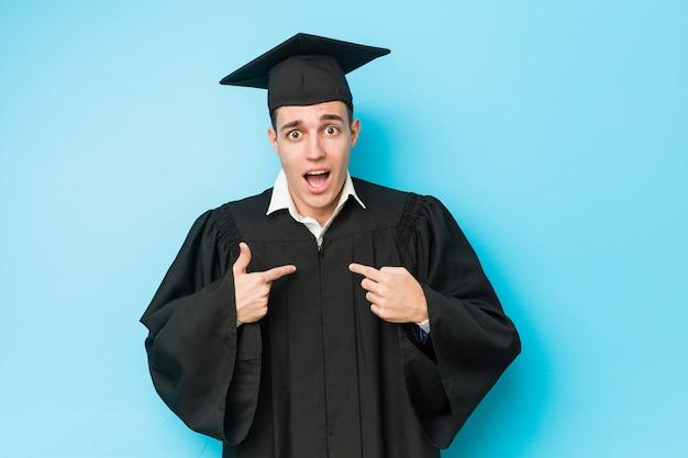 Młody kaukaski absolwent mężczyzna zaskoczył, wskazując na siebie, uśmiechając się szeroko.