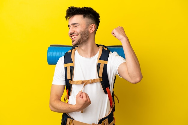Młody kaukaski alpinista z dużym plecakiem na żółtym tle świętujący zwycięstwo