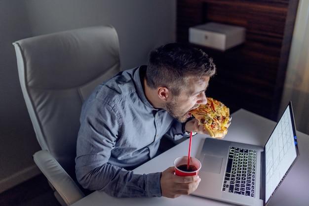 Młody kaukaski architekt je pizzę i pije sok przy biurem.