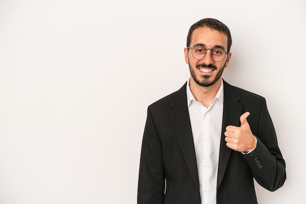 Młody kaukaski biznesmen na białym tle uśmiechający się i podnoszący kciuk w górę