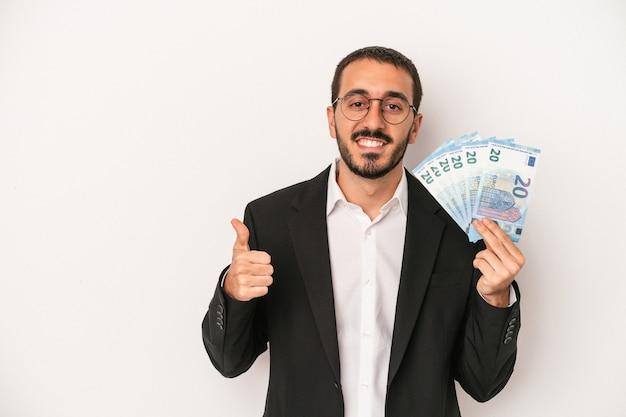 Młody kaukaski biznesmen trzymający banknoty na białym tle uśmiechający się i podnoszący kciuk w górę