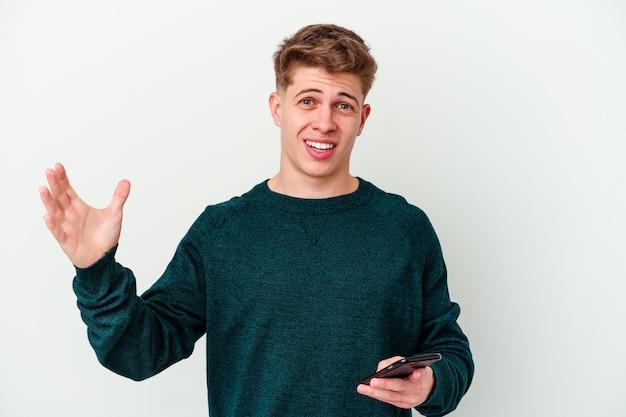 Młody kaukaski blondyn za pomocą telefonu na białej ścianie, otrzymując miłą niespodziankę, podekscytowany i podnoszący ręce