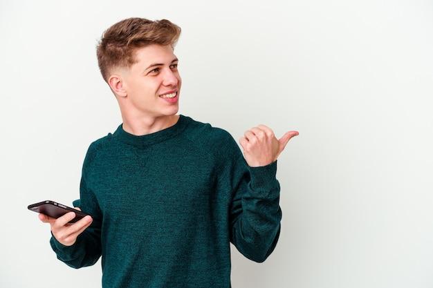 Młody kaukaski blondyn za pomocą telefonu na białym tle na białej ścianie wskazuje z dala od kciuka, śmiejąc się i beztrosko