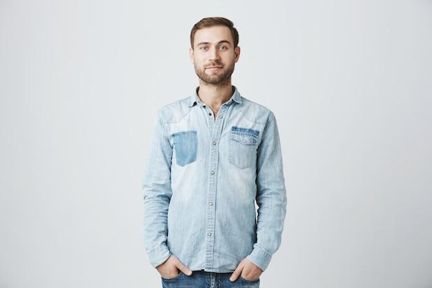 Młody kaukaski brodaty mężczyzna z rękami w kieszeniach