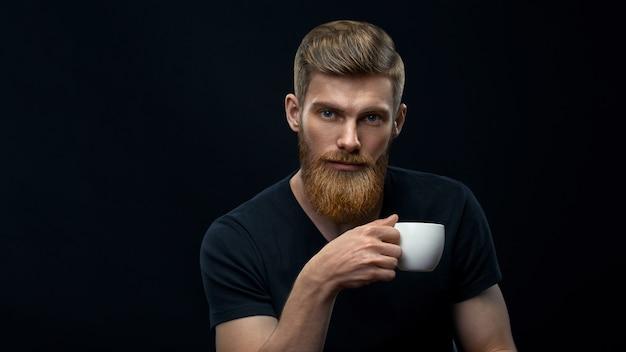 Młody kaukaski brodaty stylowy mężczyzna z filiżanką kawy. przystojny męski portret fryzury trzymając filiżankę kawy na czarnym tle.