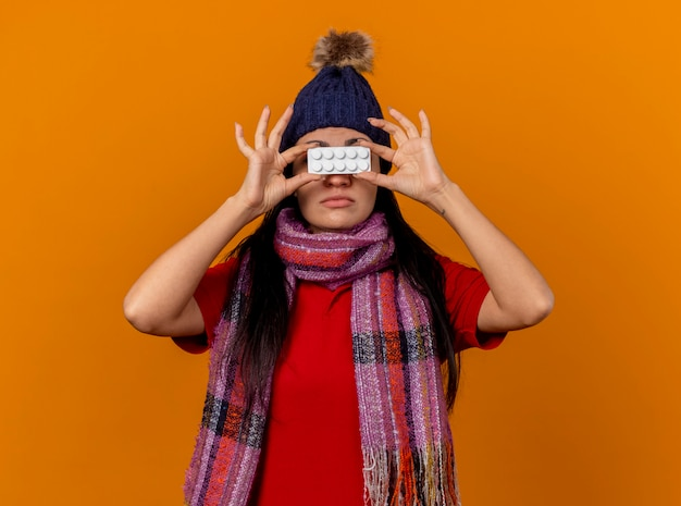 Młody kaukaski chora dziewczyna ubrana w czapkę zimową i szalik trzymając paczkę tabletek przed oczami odizolowane na pomarańczowej ścianie