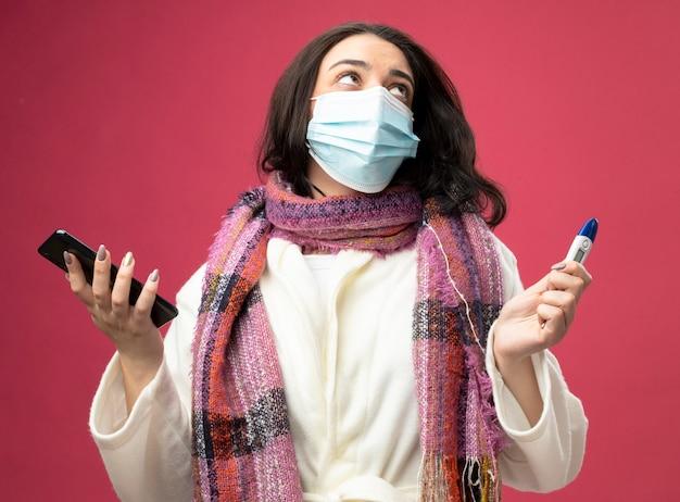 Młody kaukaski chora dziewczyna ubrana w szlafrok i szalik z maską trzymając telefon komórkowy i termometr patrząc w górę na białym tle na szkarłatnej ścianie