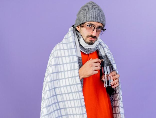 Młody kaukaski chory mężczyzna w okularach czapka zimowa i szalik owinięty w kratę trzymający lek w szkle i szklance wody na fioletowej ścianie z miejscem na kopię