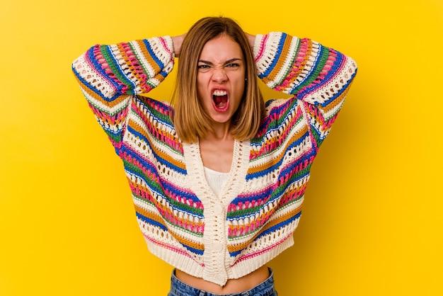 Młody kaukaski chuda kobieta na białym tle na żółtej ścianie krzyczącej z wściekłości.