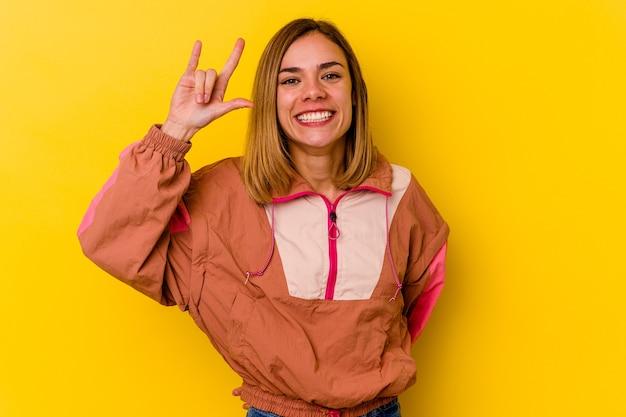 Młody kaukaski chuda kobieta na białym tle na żółtej ścianie pokazuje gest rocka palcami
