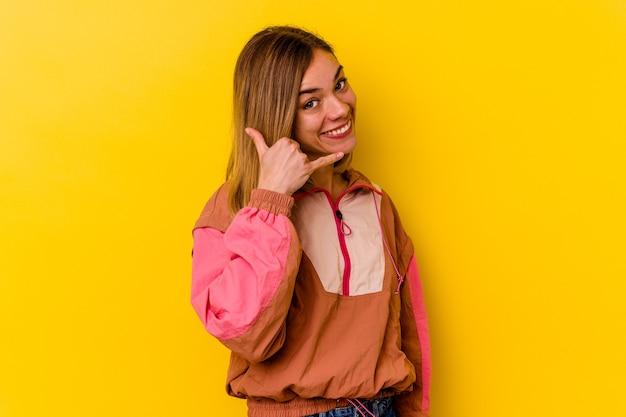 Młody kaukaski chuda kobieta na białym tle na żółtej ścianie przedstawiający gest rozmowy telefonicznej z palcami.