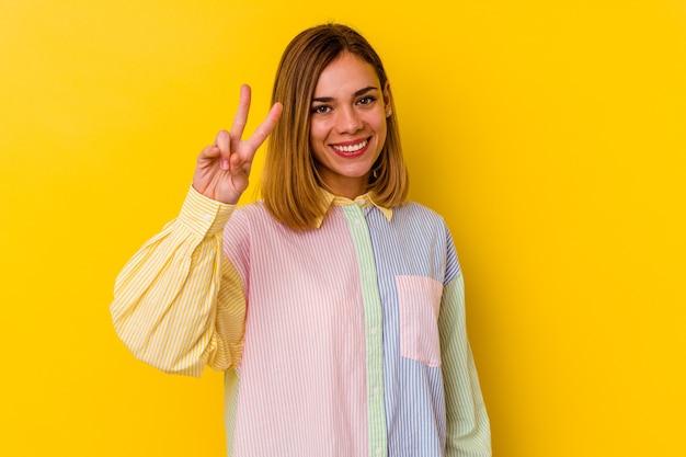 Młody kaukaski chuda kobieta na białym tle na żółtej ścianie radosny i beztroski pokazujący palcami symbol pokoju.