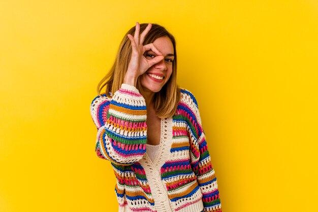 Młody kaukaski chuda kobieta na białym tle na żółty podekscytowany, utrzymując ok gest na oko.